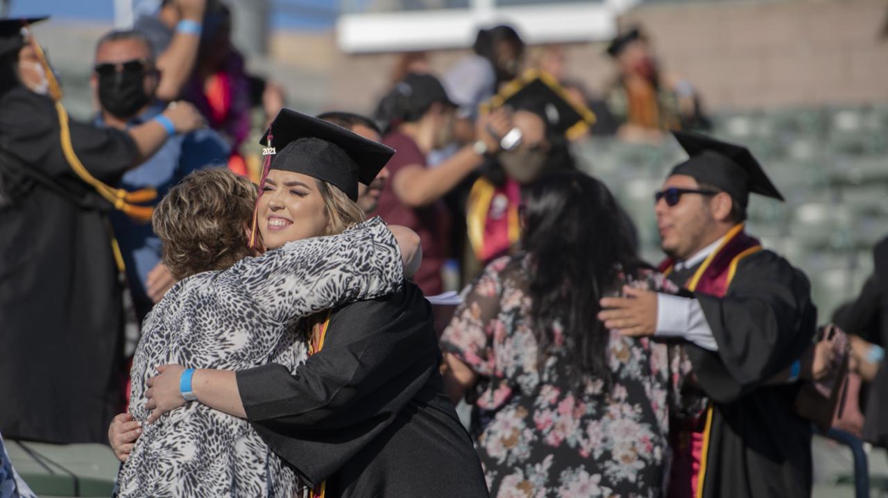 Graduate hugging relative at Commencement