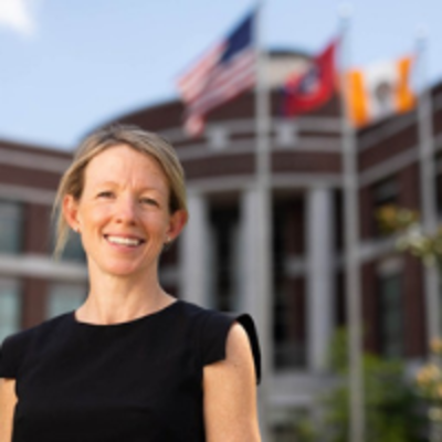 Dr. Marianne Wanamaker in focus standing in front of a blurred Howard Baker Center