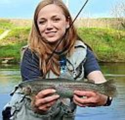 A proud female angler shows off her catch at the water's edge