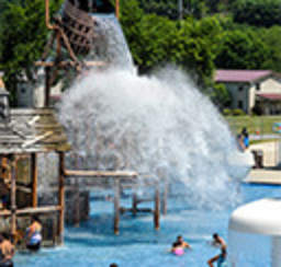 A huge spray of water crashes down on happy waterpark bathers