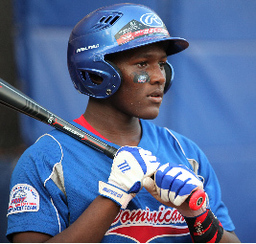 A young Dominican ballplayer in a blue uniform with a bat slung over his shoulder awaits an at-bat..