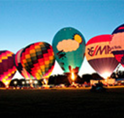 A fleet of colorful hot air balloons flaming up in preperation of take-off