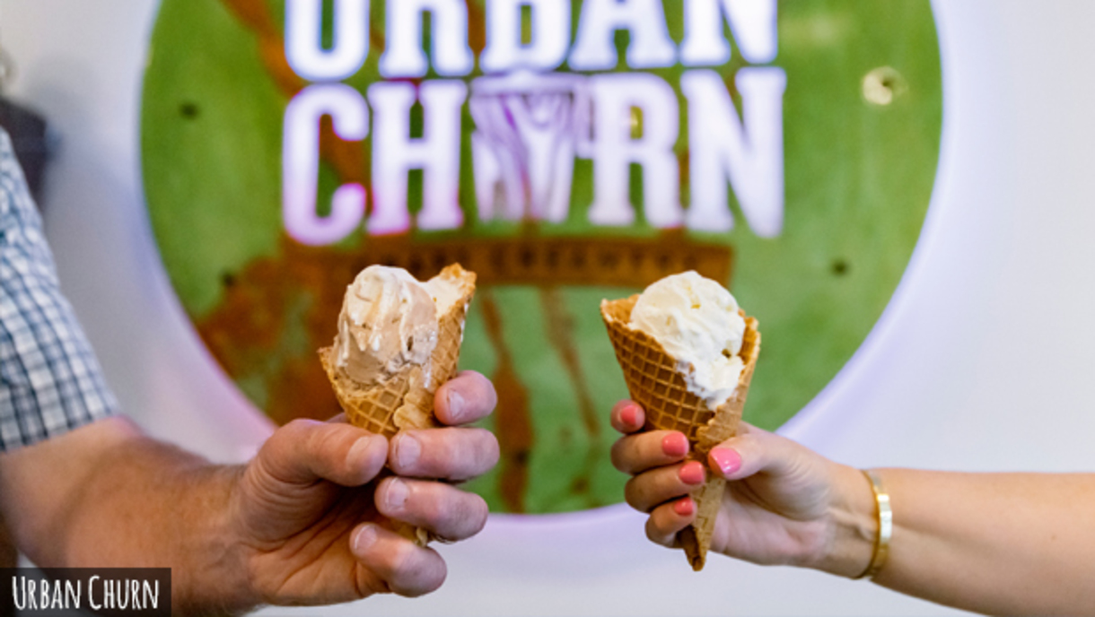 A close up shot of two different hands toasting with ice cream cones in front of a sign that read's