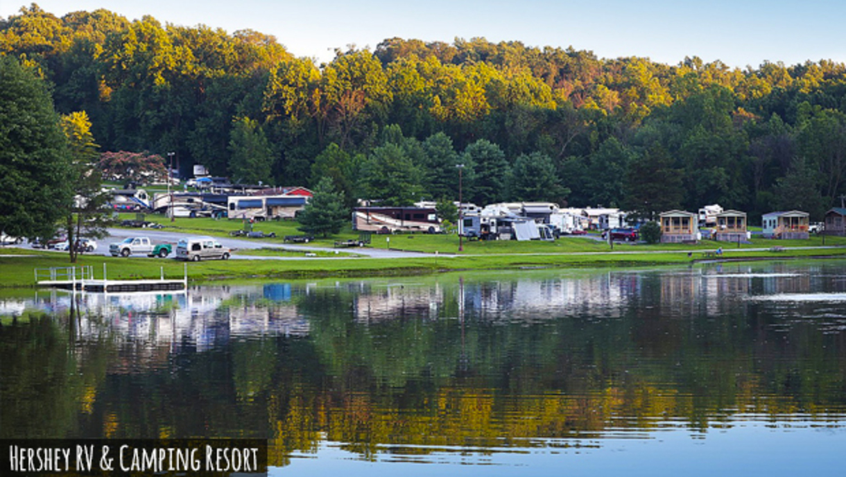 A sunset lights the tops of a lakeside treeline, casting a reflection of the Hershey RV & Camping Resort on the calm water