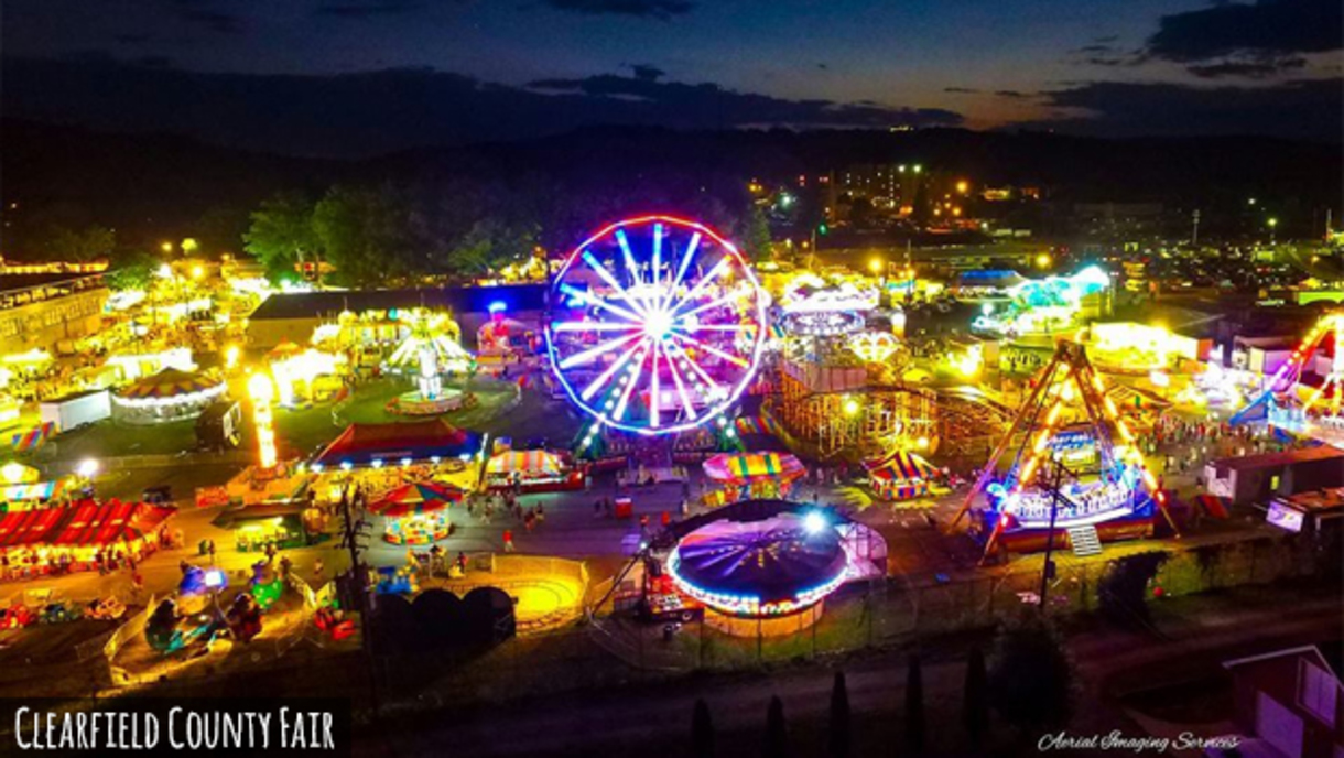 A colofully lit Clearfield County Fairgrounds with a dusky sky bustles with activity