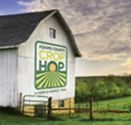 A whitewashed wooden country barn with a Crop Hop sign on its side.