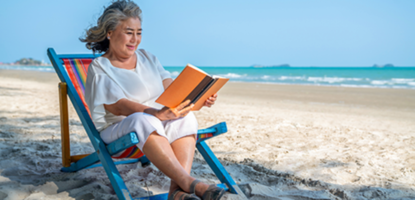 Woman sitting in chair on the beach reading a book, link to adult summer reading