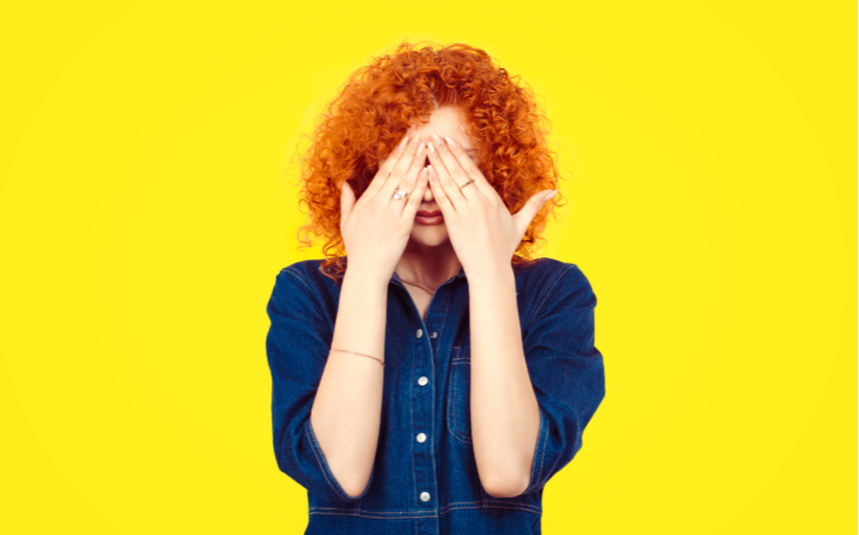 Photo of red haired woman with her hands over her eyes.