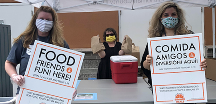 Library staff holding signs that read Food Friends, link to free summer lunches