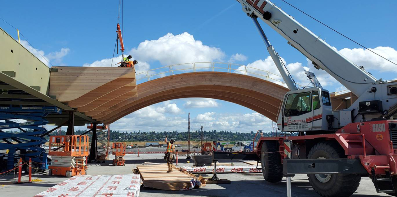 At a job site near the airport, construction crews build segments of the wooden roof for the new main terminal