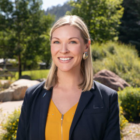 Melissa Mount sitting beneath the trees of the Fort Lewis College campus