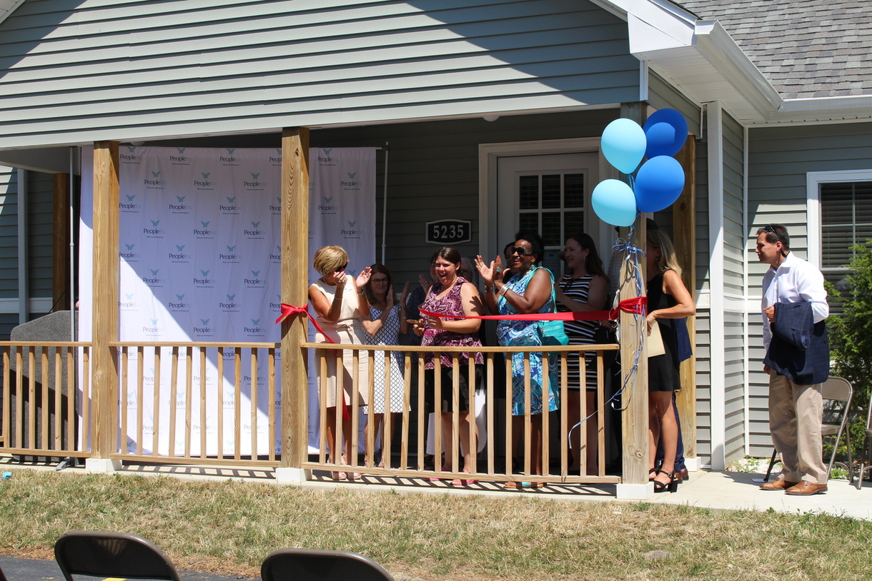 Rhonda Frederick, Rachel (who lives at Wayside) and others cutting the ribbon.