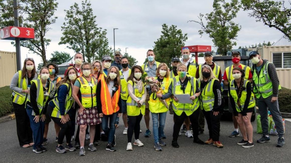 Group photo of volunteers wearing reflective safety vests and masks, posing in the Red Economy lot at PDX.