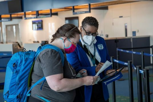 ABM employee helping a passenger at PDX figure out where to go.