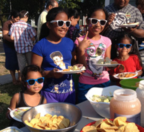Children eat barbecue at the park during National Night Out.