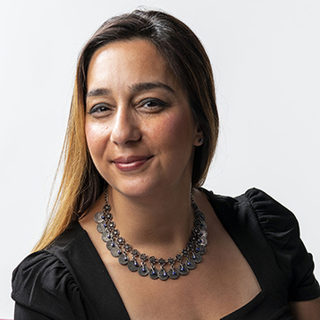 Headshot of Houra Merrikh wearing a black dress and a necklace.