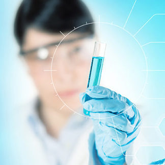 A person in a lab coat and goggles holding, with a gloved hand, a test tube with some light blue liquid in it. The hand is in focus and the person is blurry in the background.