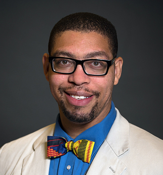 Headshot of Antentor Hinton wearing eye-glasses, a blue shirt, multi-colored bow tie, and a white coat.