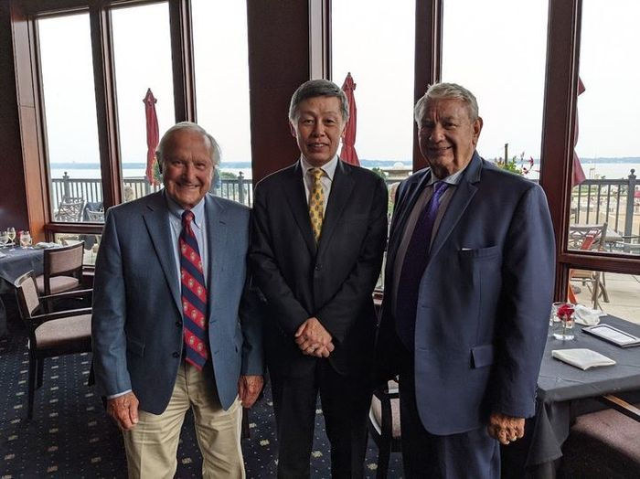 Consul-General Okada standing between Mr. Tommy Thompson and Mr. Milton Neshek in a restaurant