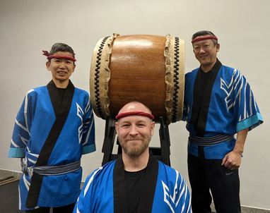 three taiko drummers in traditional clothing posing near taiko drum