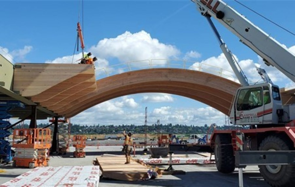 An enormous curved wooden beam being worked on a constrcution site.