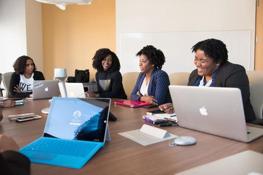 4 women at conference table working on laptops