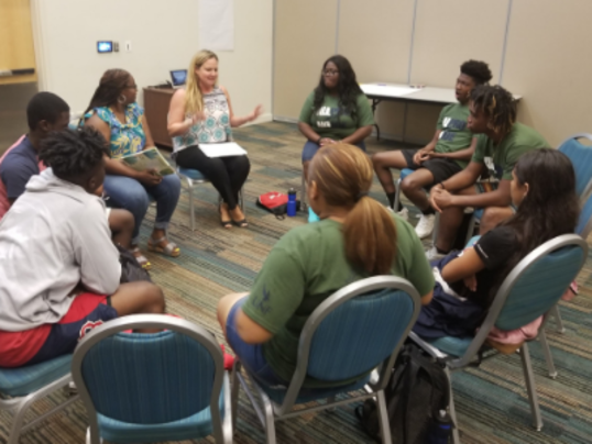 Group of bridges campers sit in a circle with two mentor leaders