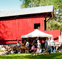 Festival goers walking by a vendor's tent set up beside a covered bridge.