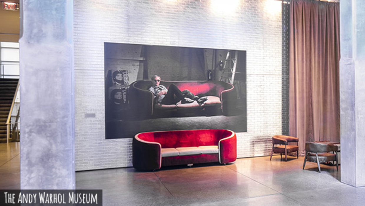 A red velvet sofa sits below a life size portrait of Andy Warhol on the same red velvet sofa.