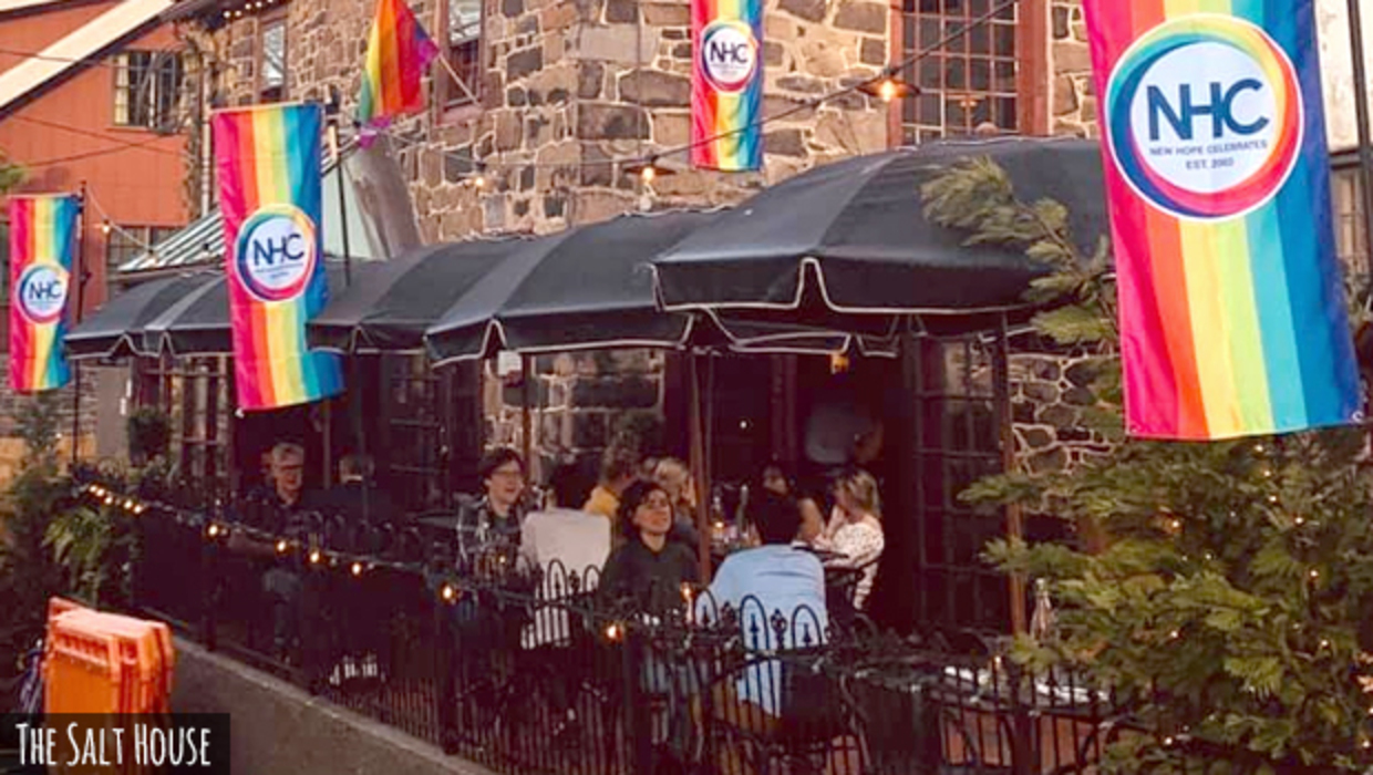 Pride parade flags adorn the al fresco diners eating outside the stone walls of The Salt House gastropub in New Hope