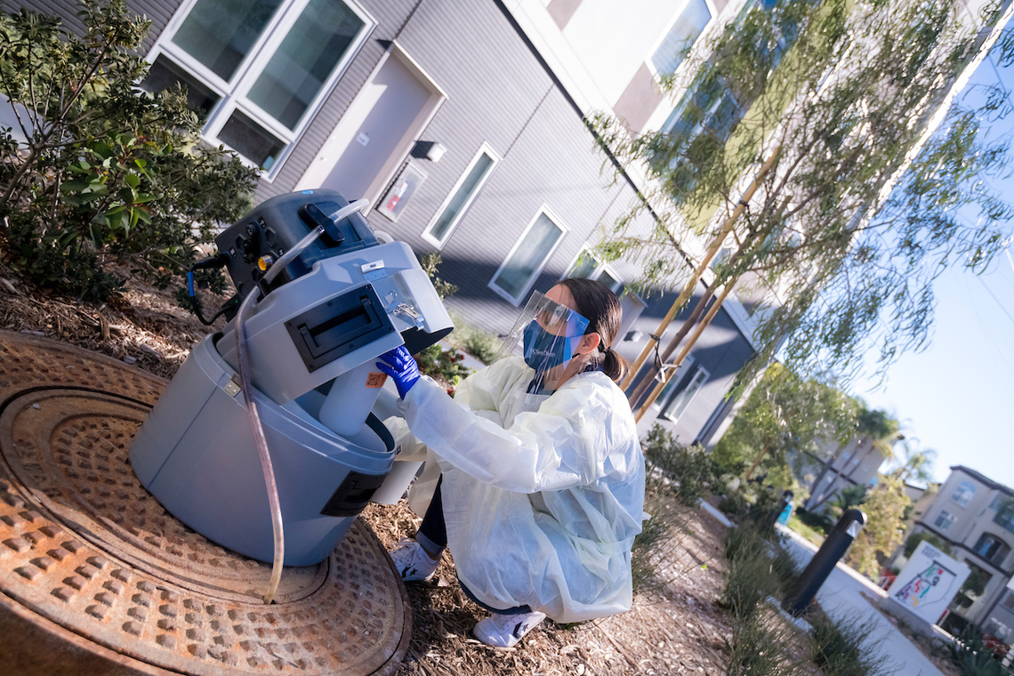 UC San Diego student taking a wastewater sample to detect any COVID-19 cases on campus