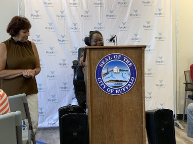 A resident speaking at a podium at the event.