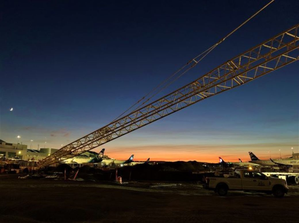 Giant crane at PDX, on the airfield there are planes in the background and the sun is setting.