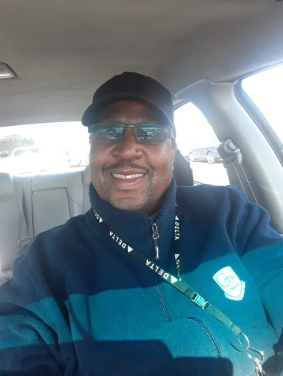 Jimmie Hudson, smiling and wearing a jacket with a G2 Secure Staff emblam.