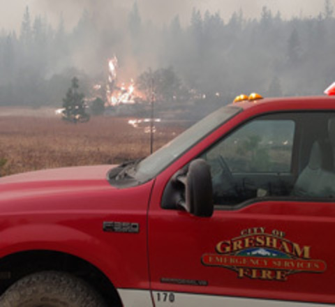 Wildfire burns within view of a Gresham Fire truck.