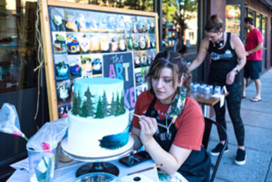 Decorating a cake for people watching at Third Thursday downtown.