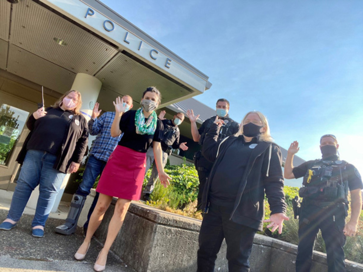 City Manager Nina Vetter and Police staff wave to the camera outside the station.