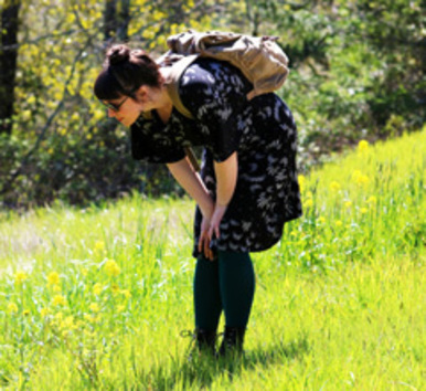 A woman inspects the native plants on Hogan Butte.