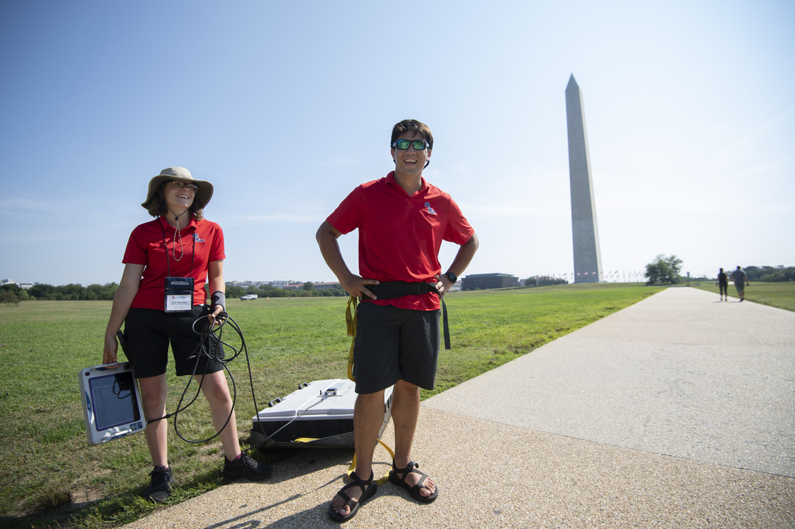 Two dressed in Red OleMiss collard shirts holding and standing in front of equipment at the Washington Monument