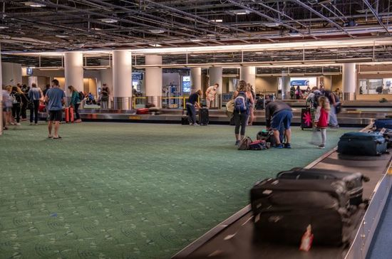 Baggage claim at PDX - travelers collecting luggage coming off of the baggage carousel.