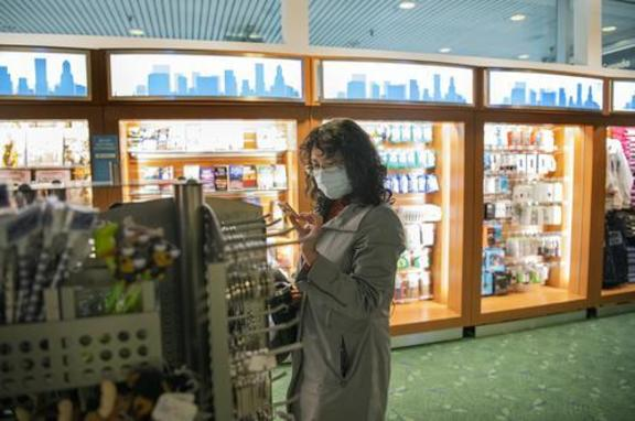 Woman shopping at Your Northwest Travel Mart at PDX. She is wearing a face mask.