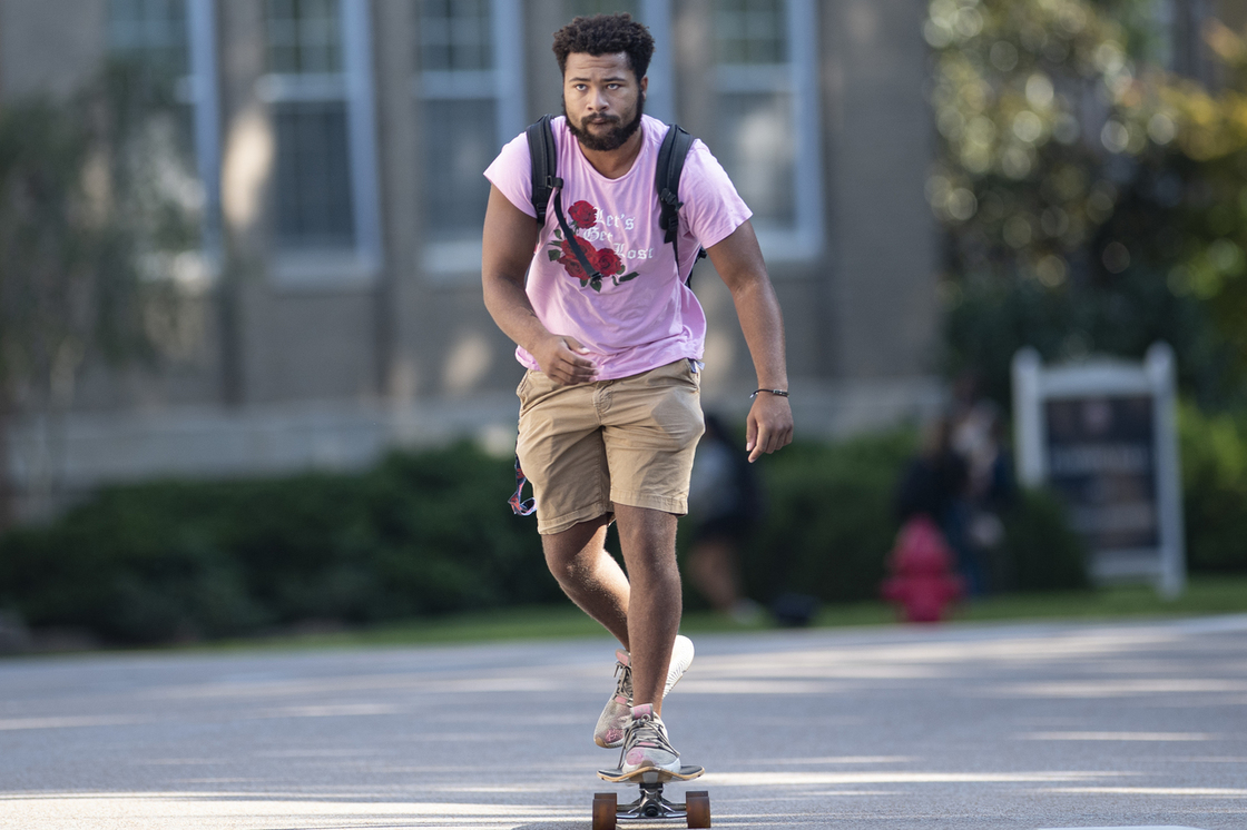 Student in a pink tshirt and kahki shorts skateboarding on campus