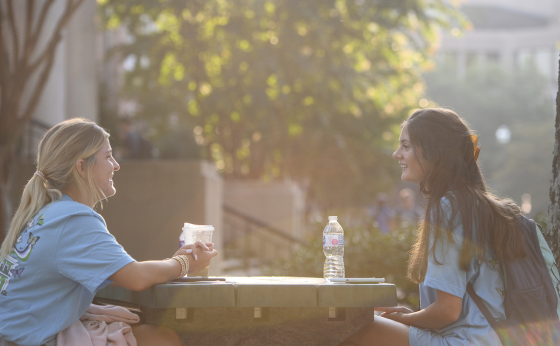 Two students sitting at a table outdoors smiling and talking to each other having drinks