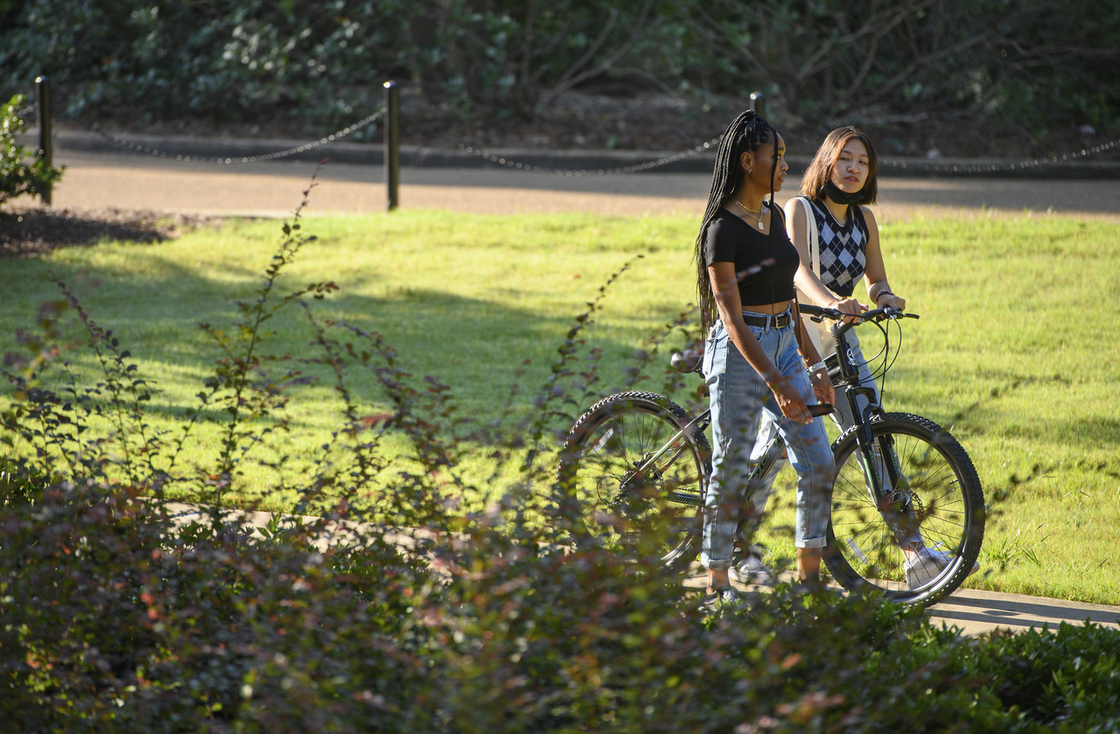 Two students walking; one with a bike