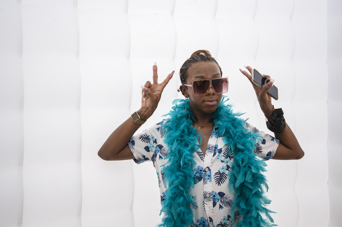 Student in photobooth wearing a teal feather boa holding up two peace signs