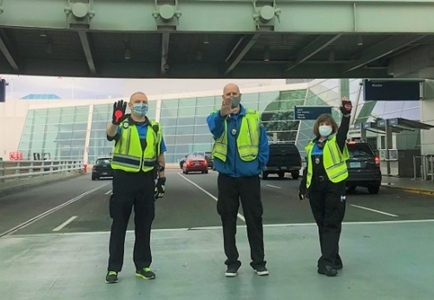 Three parking control representatives, wearing high-visibility vest, face masks and holding up their hands in a
