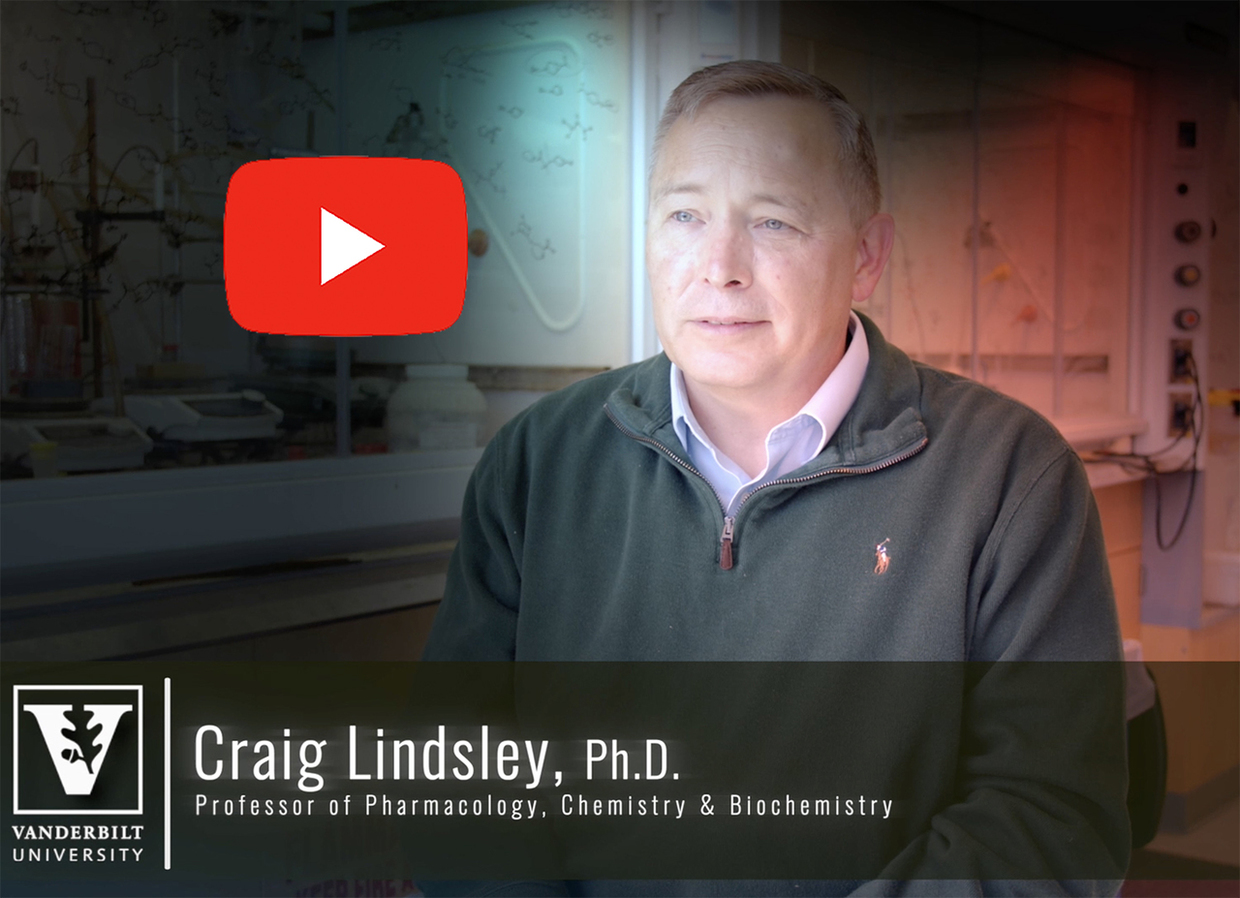 Screenshot of Craig Lindsley, seated in a lab wearing green sweater. The background is distorted.