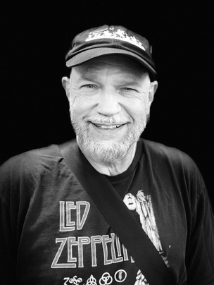 Black and white photo of Marc Wozniak wearing Led Zeppelin tee-shirt and a cap.