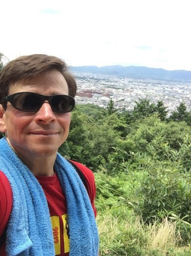 Image of Dan Carolin, wearing black sunglasses on mountain top overlooking a city in Japan