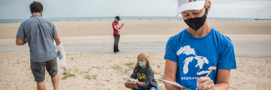 images of people in masks cleaning up the beach at Lake Michigan
